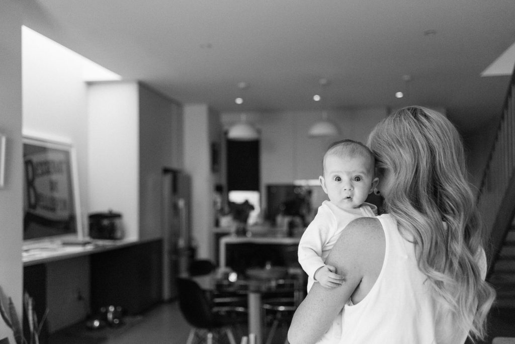 Blonde haired mother holding baby over her shoulder in their kitchen