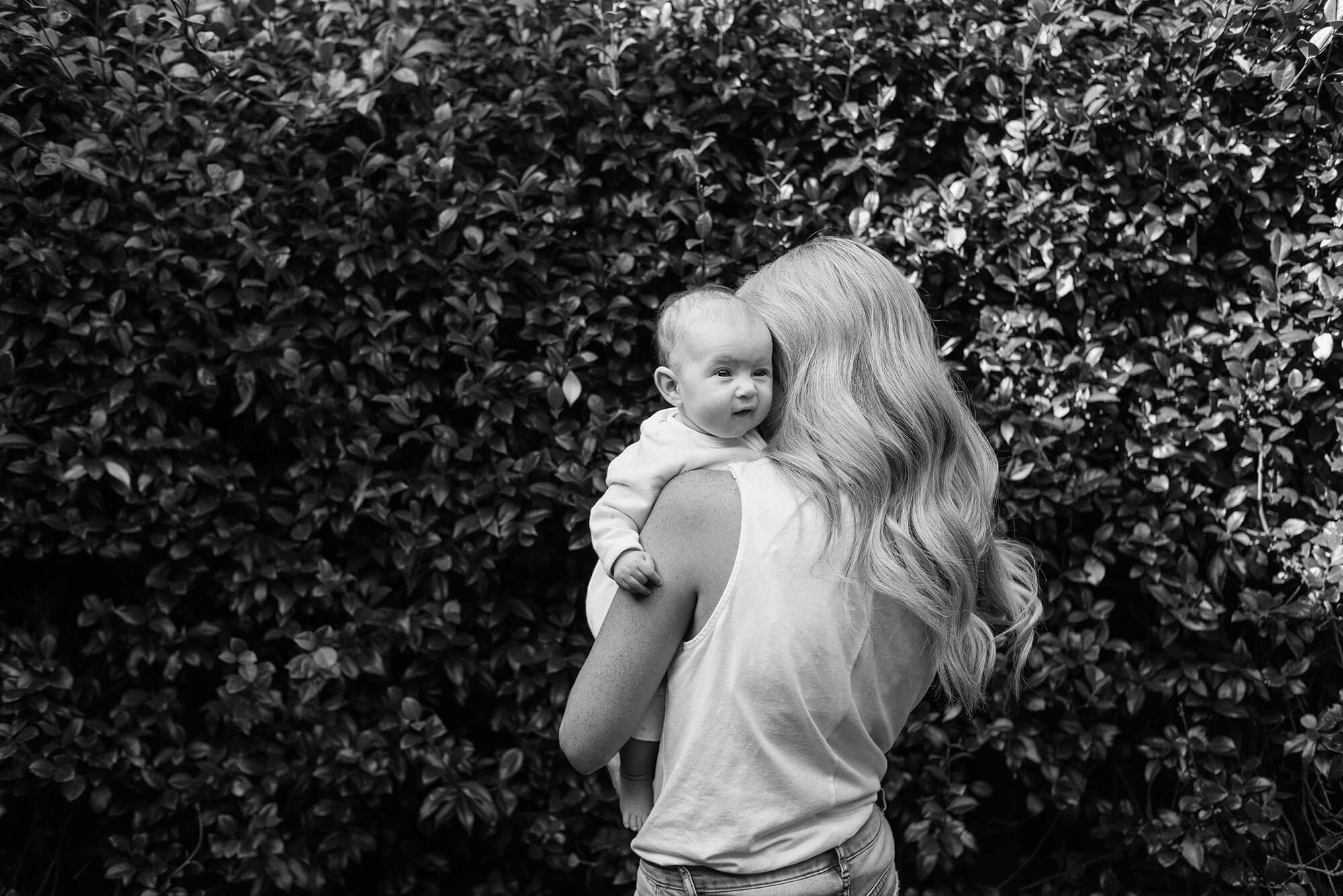 Mother with long blonde hair holding baby girl who is looking out over her shoulder