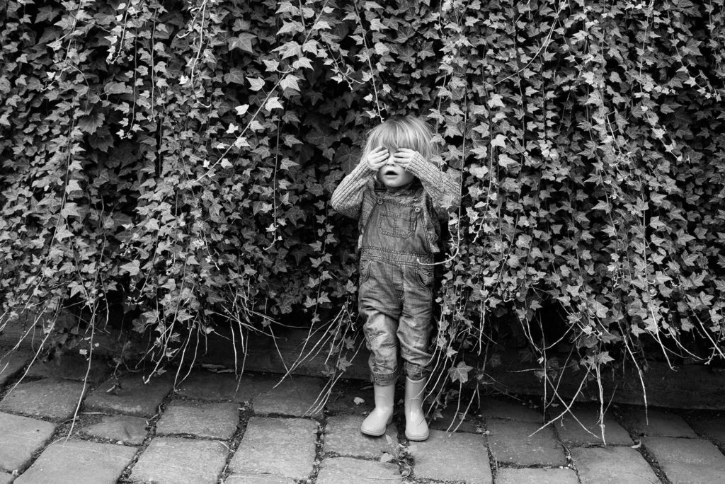 little boy wearing gumboots and overalls covers eyes and is hiding in ivy vine