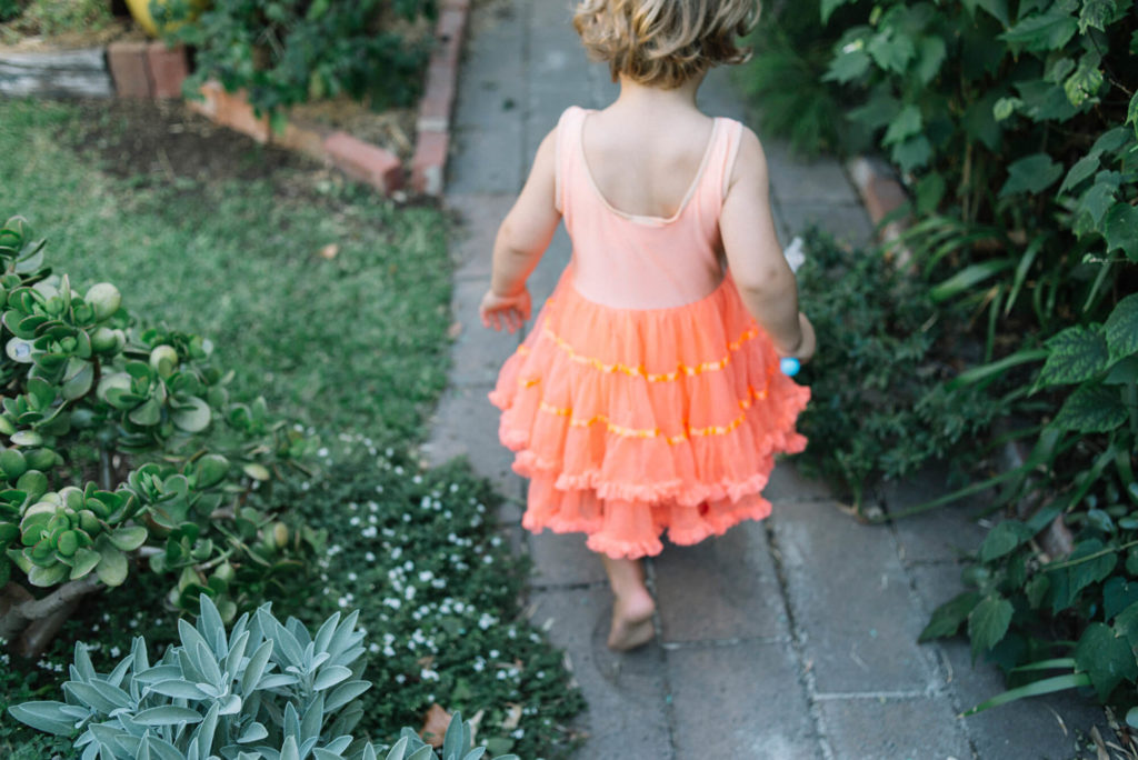 Young boy in orange fairy dress walking down garden path with green plants either side