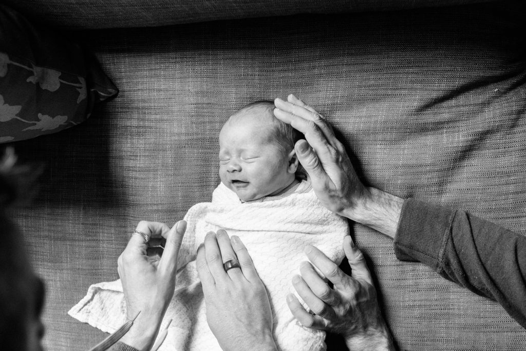 Newborn baby being wrapped in swaddle by Dad's hands