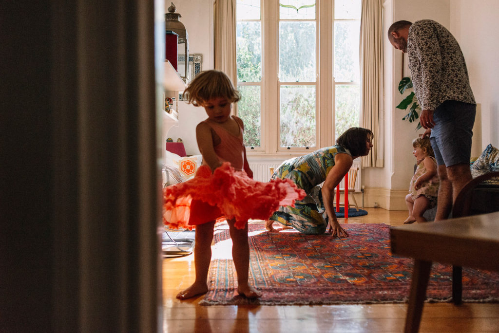 Two parents and two children dancing in their living room. Little boy twirling in an orange skirt