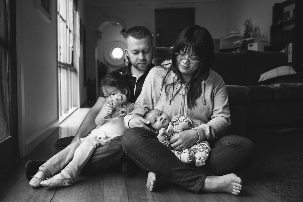 Portrait in Black and white of parents, toddler and baby sitting on living room floor