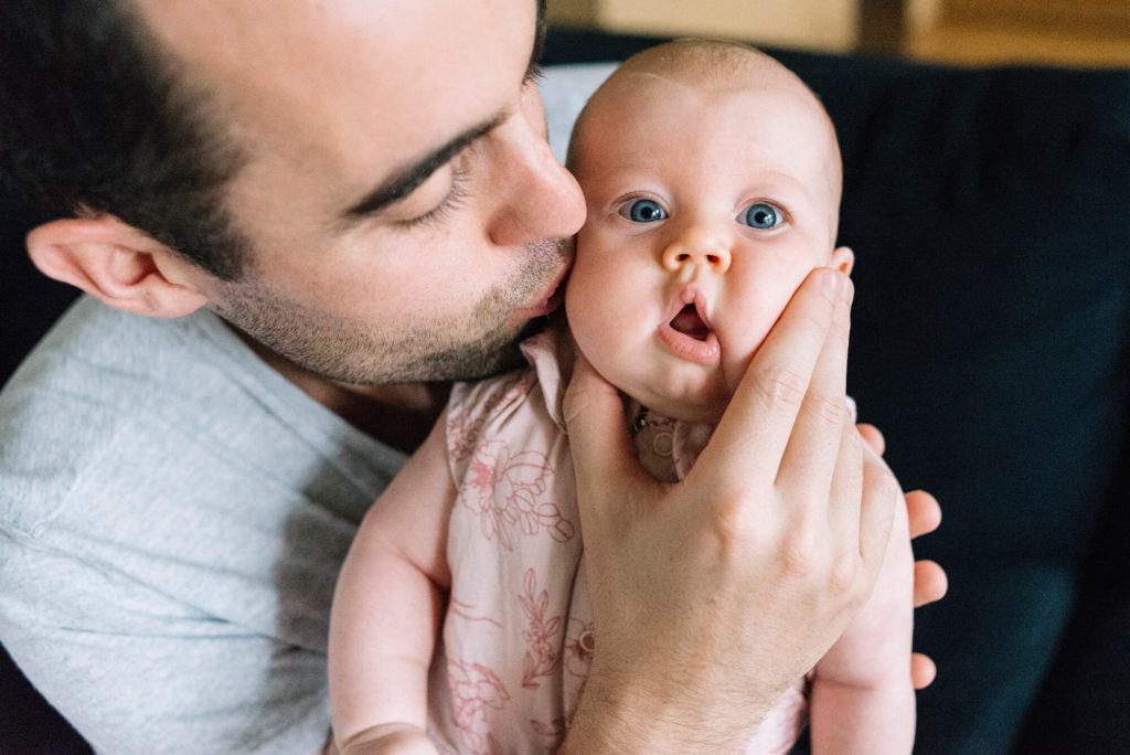 Father squishing blue-eyed baby's face in his hand while kissing her