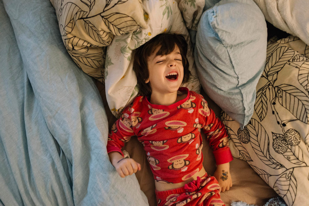 Laughing toddler on bed in red monkey pyjamas
