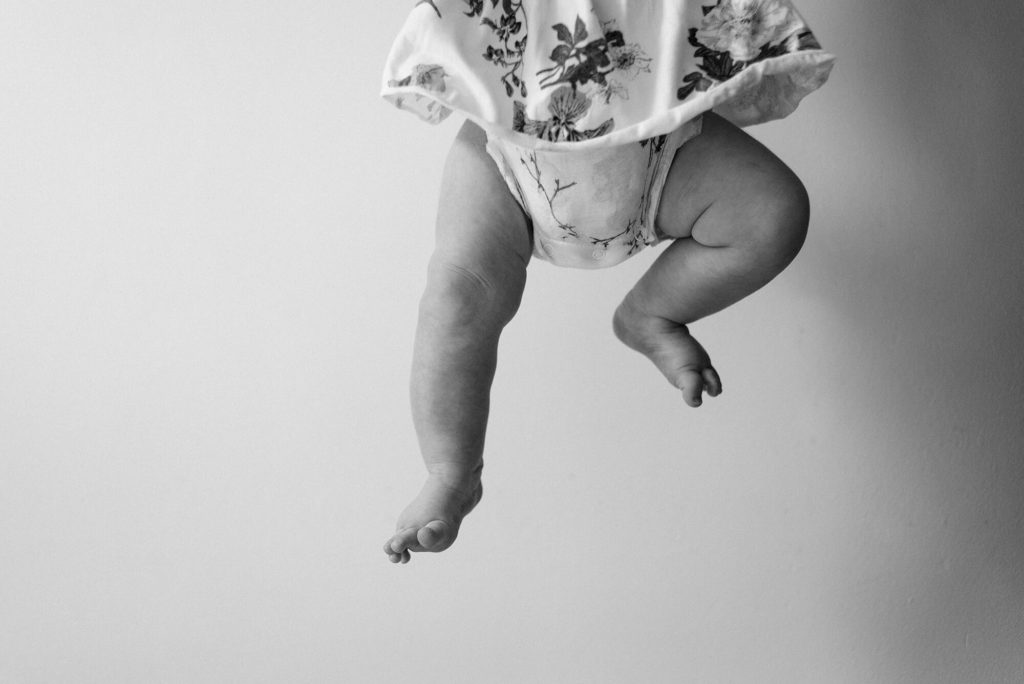 Baby wearing floral dress with chunky legs dangling in black and white
