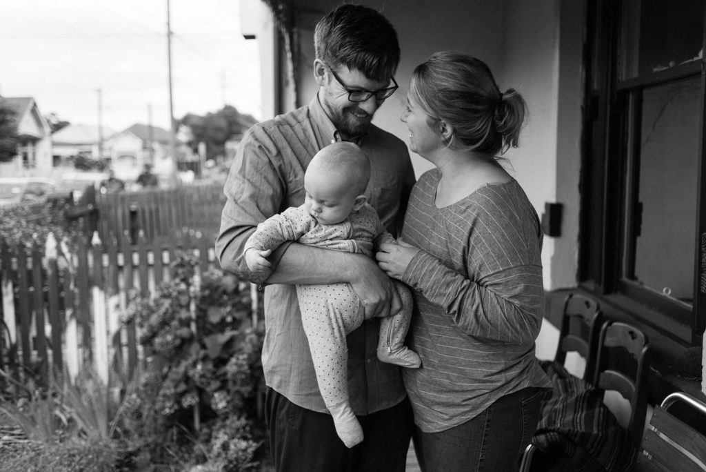 New parents laughing while holding baby boy on front verandah