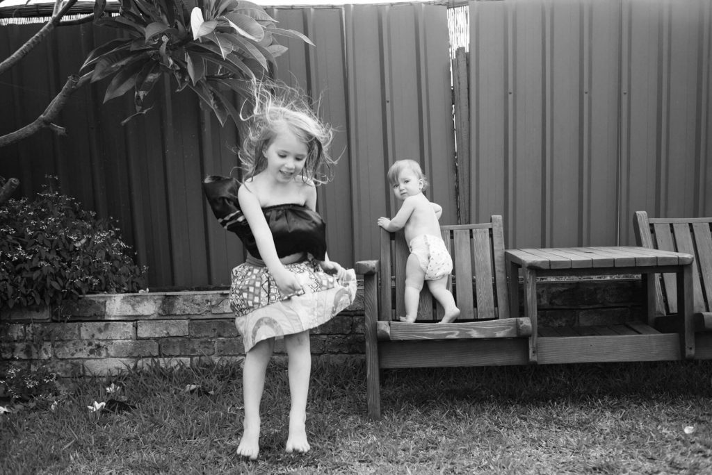 Sisters playing in backyard with older girl jumping while baby climbs on chair