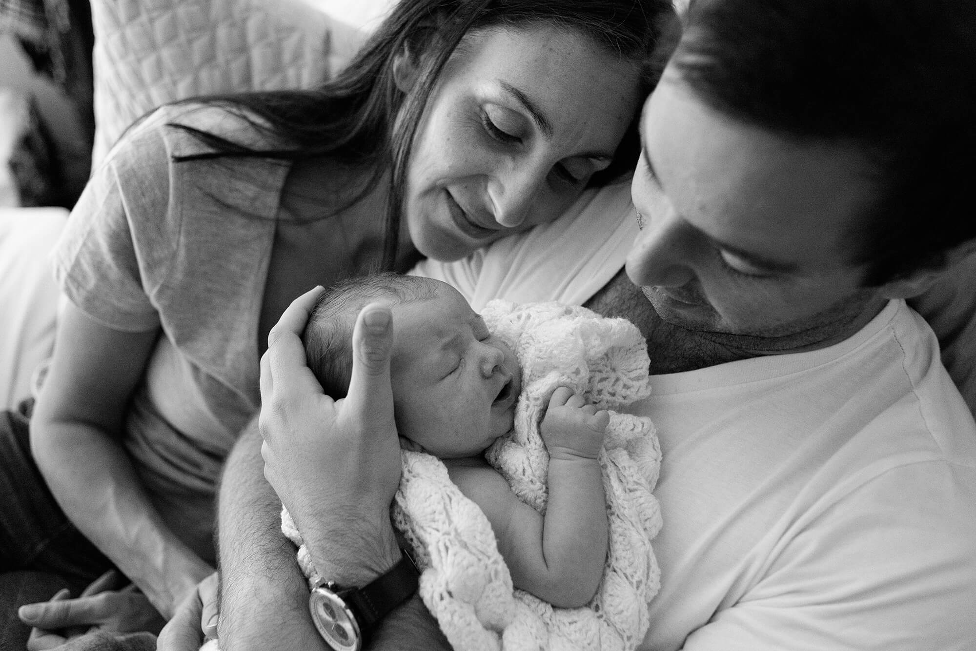 Parents snuggling newborn baby wrapped in blanket with fathers hand cradling head