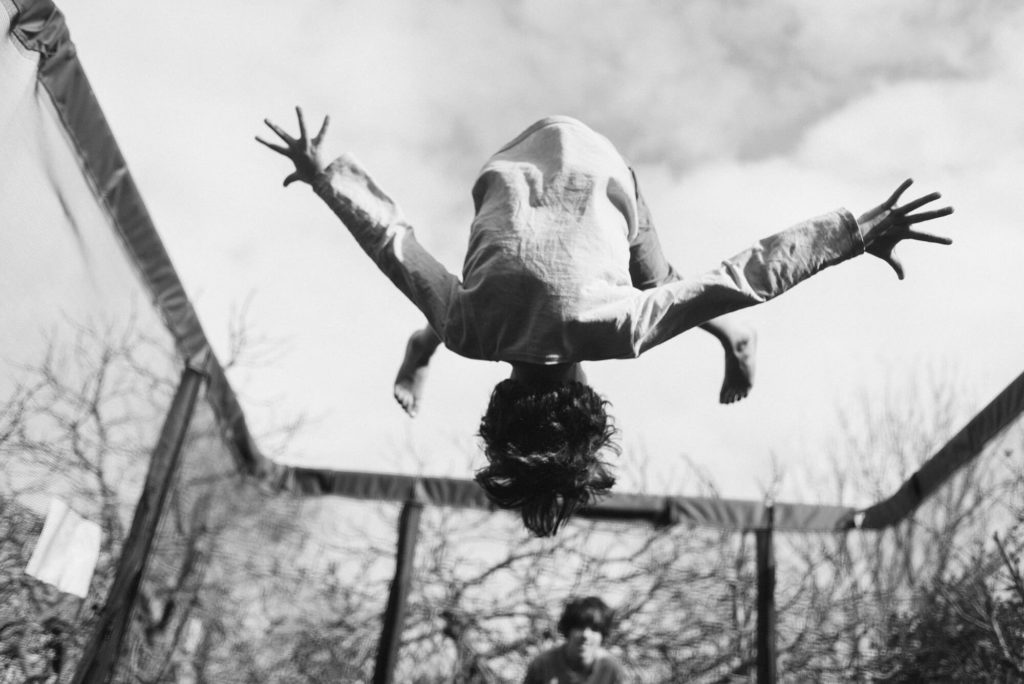 Young child turned upside down on trampoline