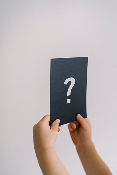 childs hands holding black piece of paper with a question mark