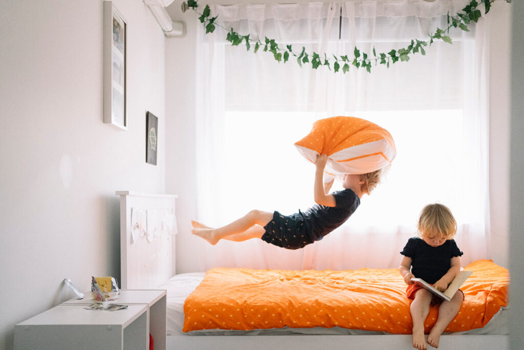 Boy-jumps-backwards-onto-bed-while-sister-reads-on-bed