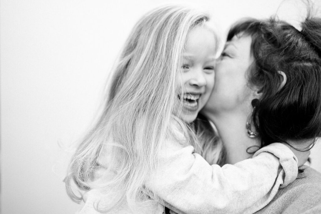 mother-whispers-into-laughing-daughters-ear