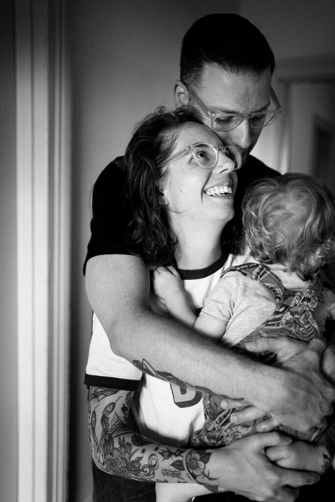 Family-of-three-embrace-mother-smiles
