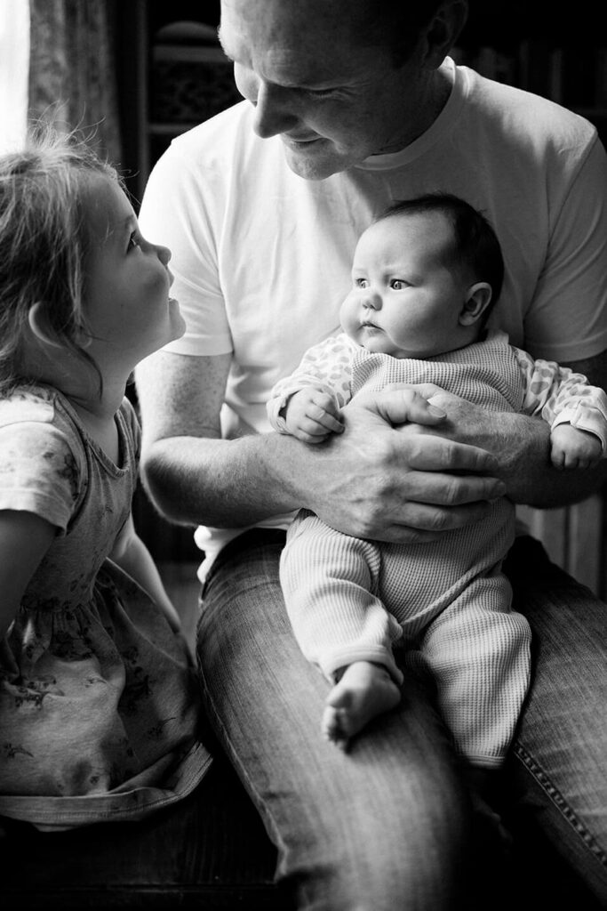 black-and-white-image-of-father-talking-to-daughter-while-holding-baby-on-knee