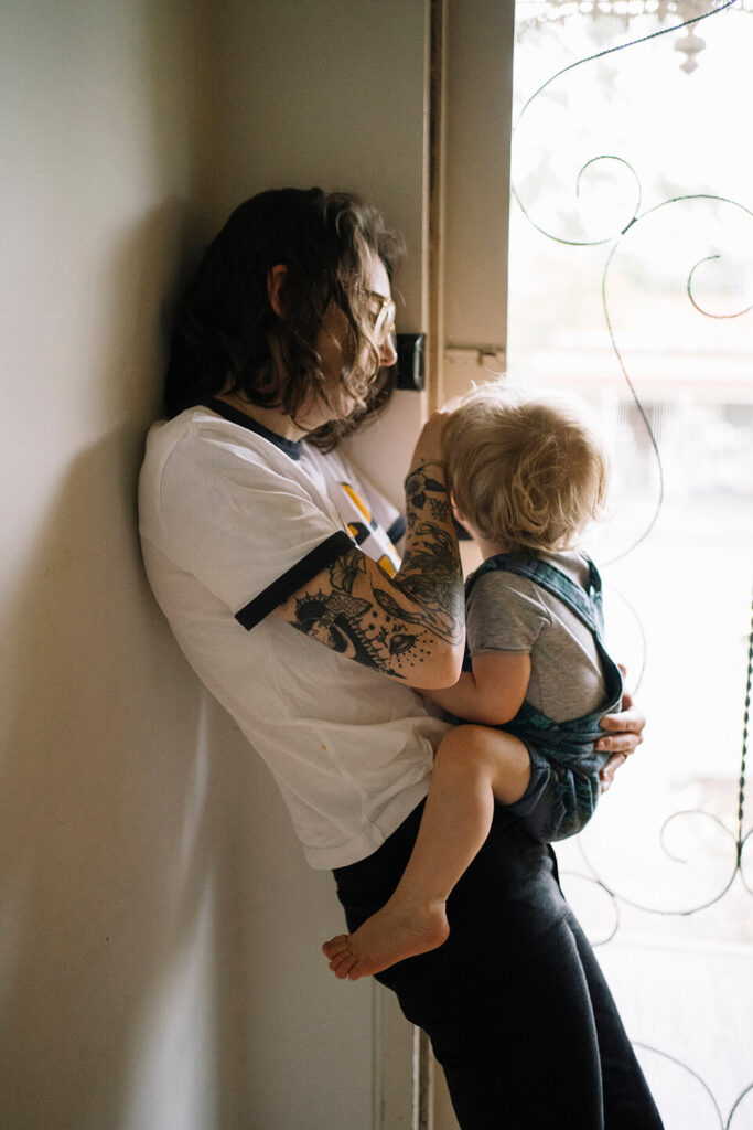 mother-holding-toddler-leaning-against-wall-in-hallway