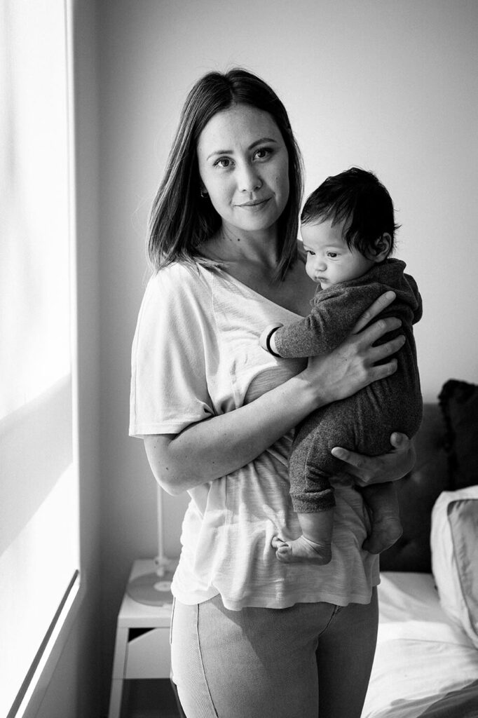 mother-looks-at-camera-holds-child-in-bedroom